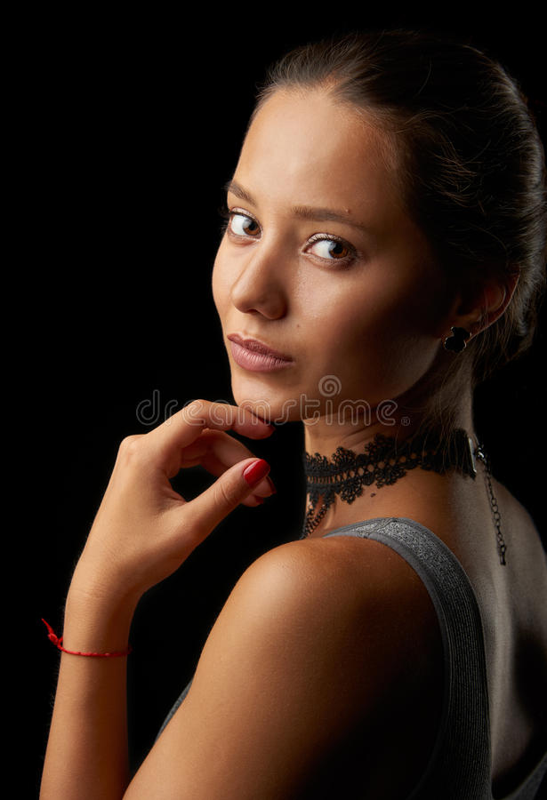 Very beautiful girl. Portrait. Looking over the shoulder on black background royalty free stock photos