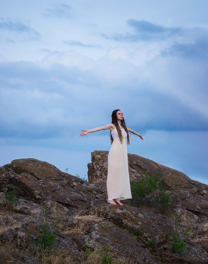 A beautiful girl in a white dress with dreadlocks is standing on a cliff with her arms outstretched against a cloudy sky at sunset royalty free stock image