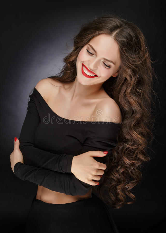 Very beautiful glamor girl with plush healthy curly hair laughing, portrait royalty free stock photography