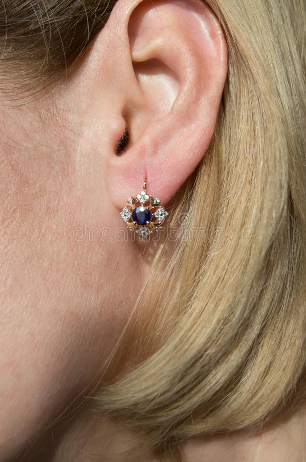 Very beautiful golden earring with dark blue gem - sapphire and stock image