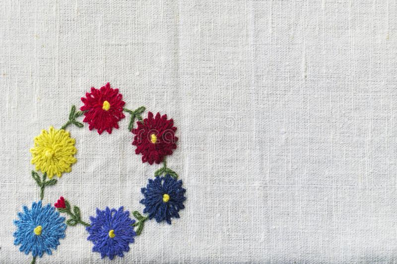 Very beautiful  hand embroidery. Embroidered yellow, red  and blue flowers on a white fabric royalty free stock image