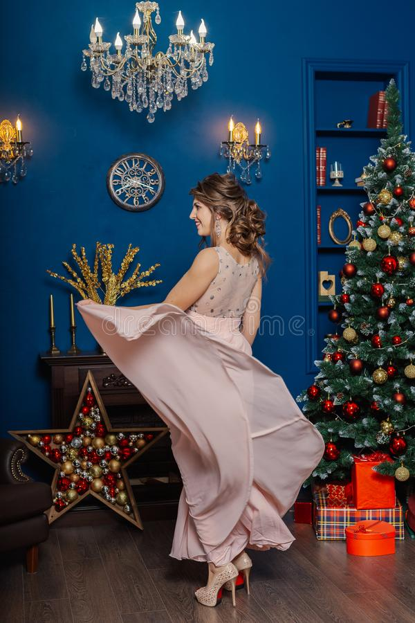 Very beautiful and woman in a pink dress in New Year`s decor. royalty free stock photo