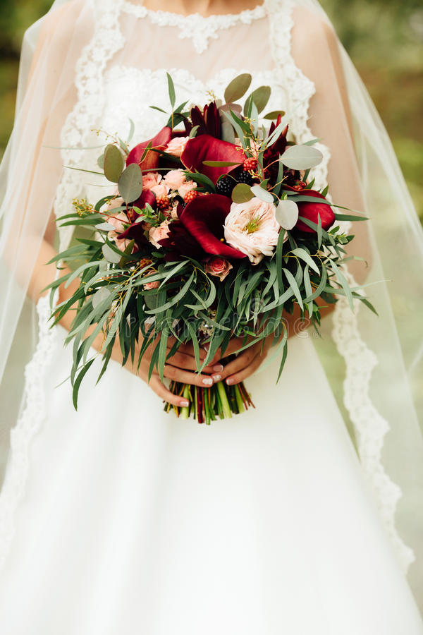 Very beautiful wedding bouquet in hands of the bride stock photography