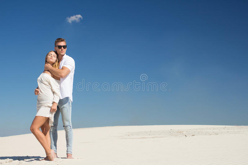 A very beautiful young couple is standing under a clear sun among the white sands royalty free stock photography