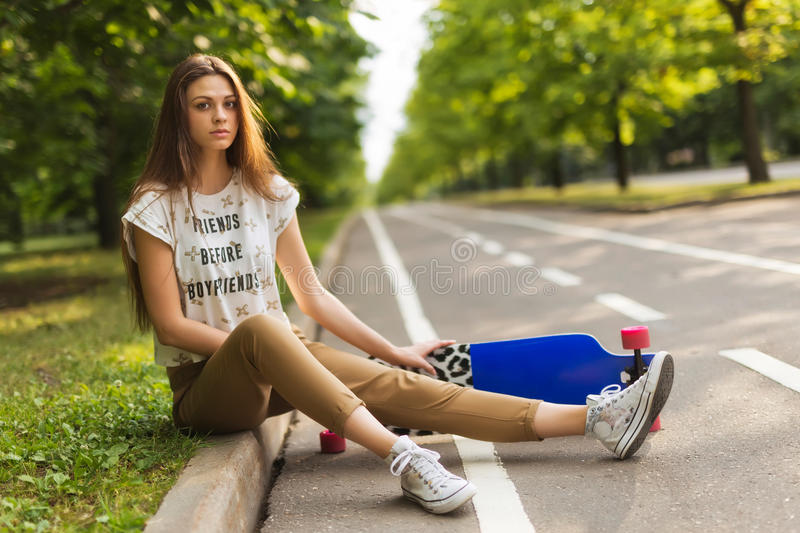 Very beautiful young girl with long hair sitting in the park on the track and keep lorgbord. Skateboarding. lifestyle stock images