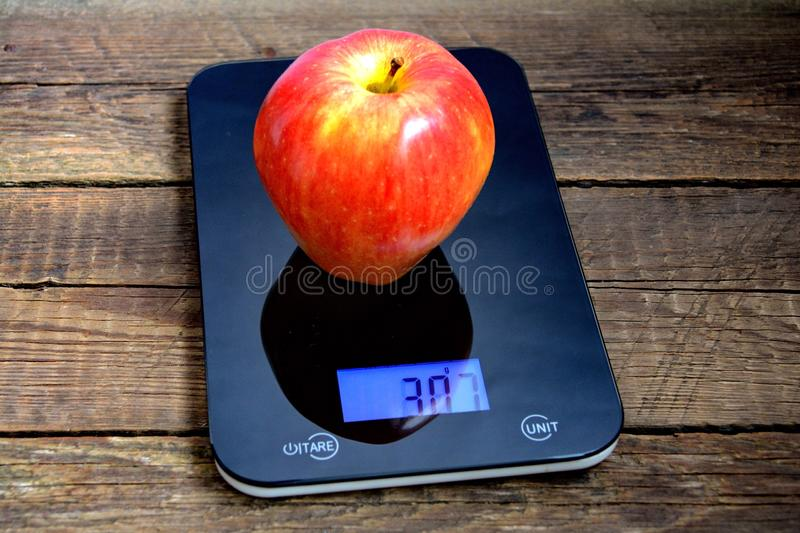 Apple on scales. The best diet for weight loss, big apple on scales stock photography