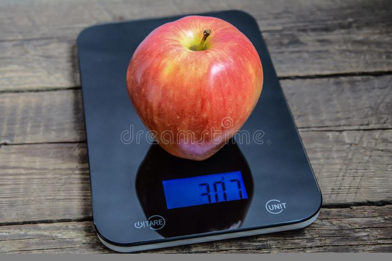 Very big apple on scales. Big red apple on scales royalty free stock photography