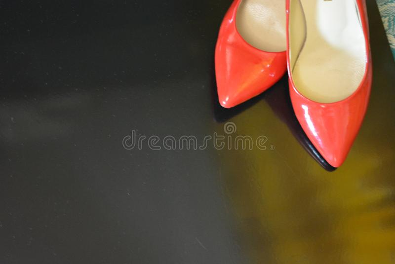 A very bright pair of shoes, fashionable and stylish women`s red shoes with a pointed toe and high heels. Women`s fashion, jewelry and accessories for every day stock photos