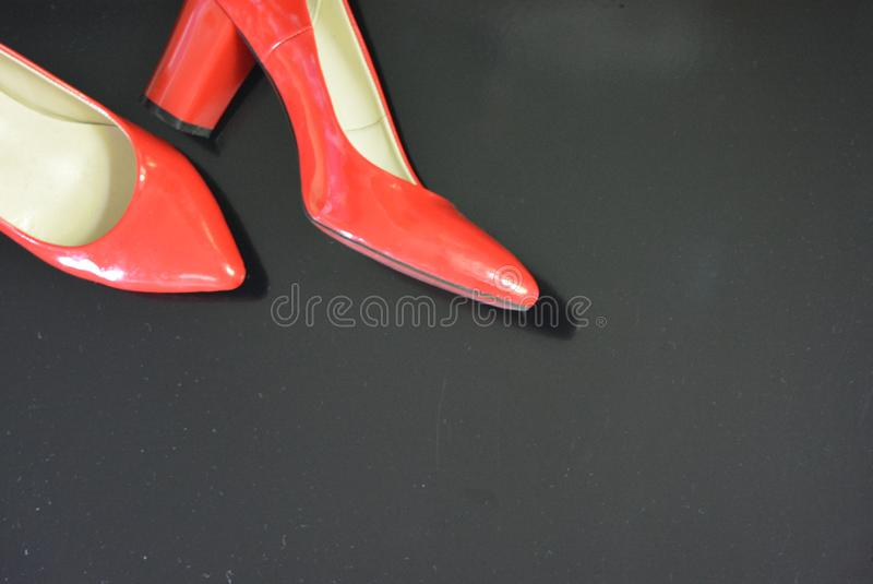 A very bright pair of shoes, fashionable and stylish women`s red shoes with a pointed toe and high heels. Women`s fashion, jewelry and accessories for every day stock image