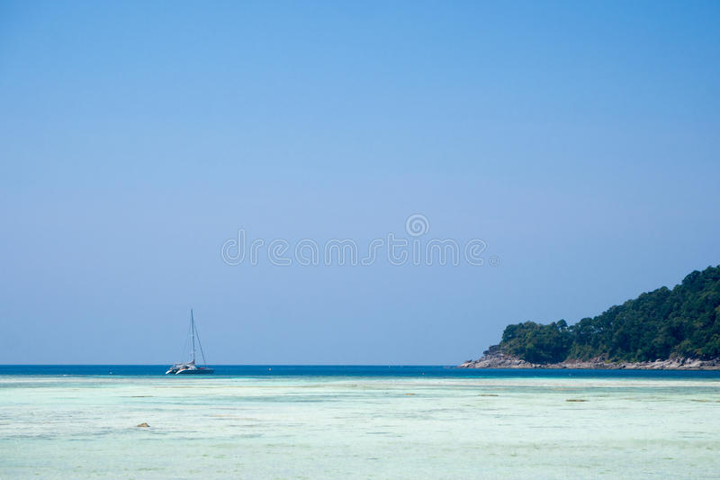 Very clean sea like as crystal clear water with boat parked in the distance. royalty free stock photography