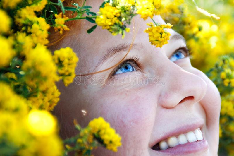 A very close portrait with an emphasis on the amazing blue eyes of a red-haired girl surrounded by bright yellow flowers. Freckles stock photo