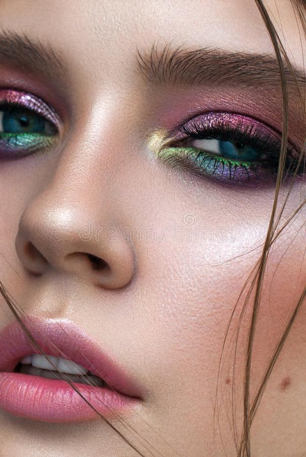 A very close up photo of young model with blue eyes, rainbow eyeshadows and perfect skin. Colorful eyeshadows. Locks on a face. Half-open lips royalty free stock photo