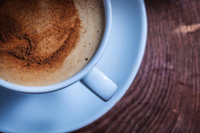 Very close up view from above coffee with foam and cinnamon in white ceramic cup on vintage cross section tree trunk stock photos