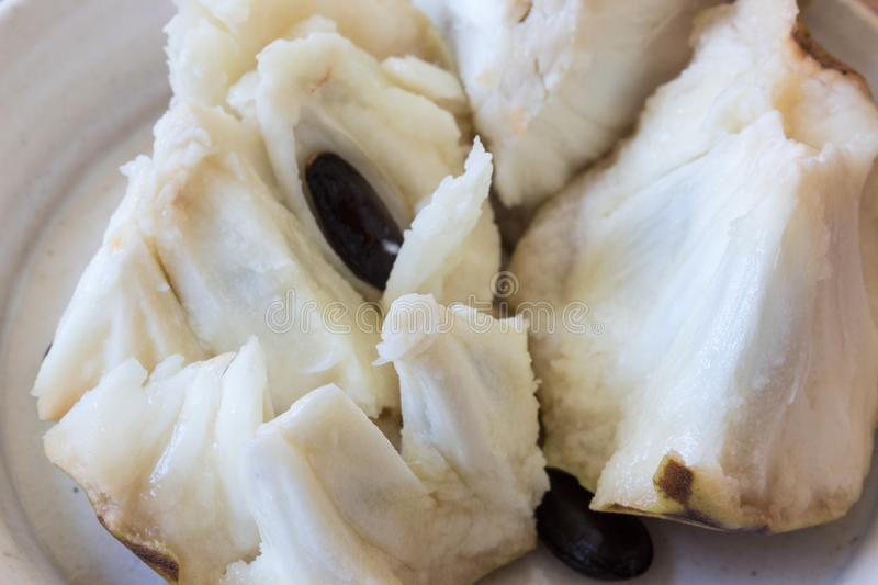 Very close view of broken apart hunks of cherimoya fruit Annona cherimola with seeds revealed royalty free stock photo