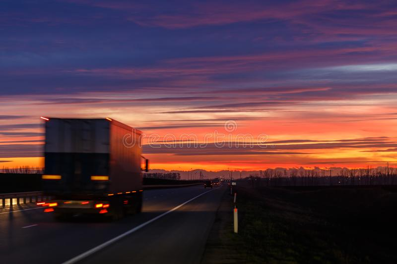 A very colorful sunset and a moving blurred truck on an asphalt road stock photos