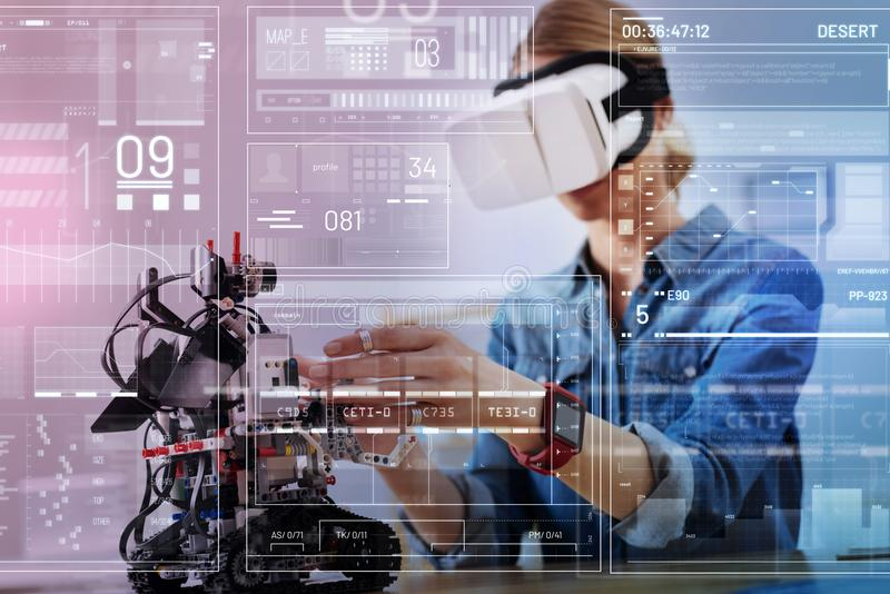 Careful engineer touching a robot while being in virtual reality glasses royalty free stock photo