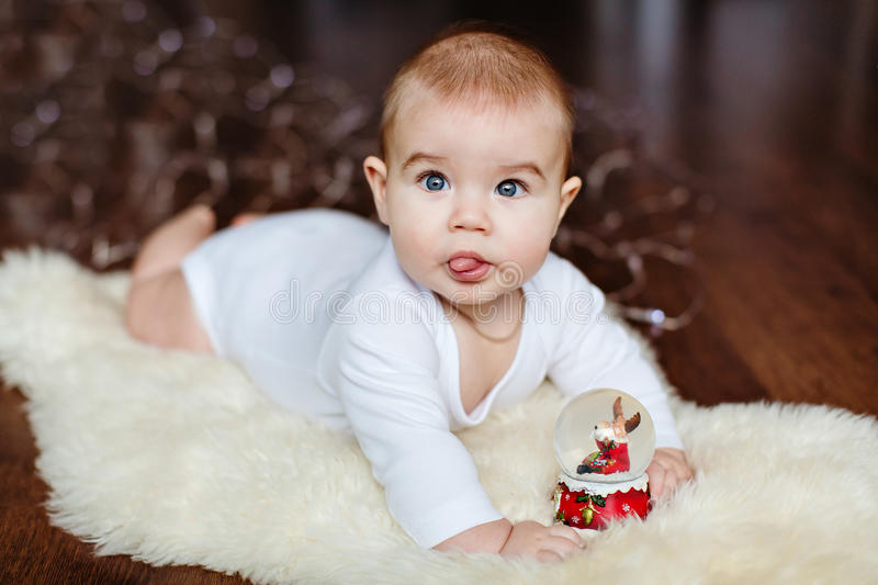 Very cute baby lying on the floor on the background of Christmas stock image