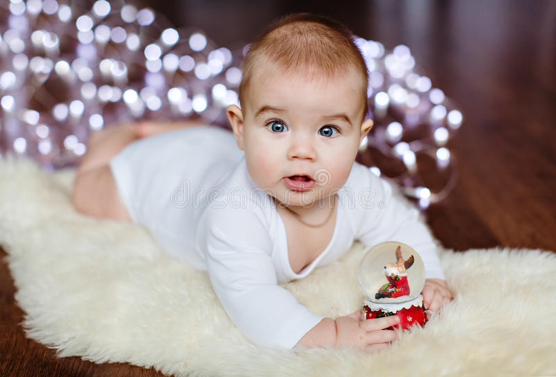 Very cute baby lying on the floor on the background of Christmas royalty free stock photography