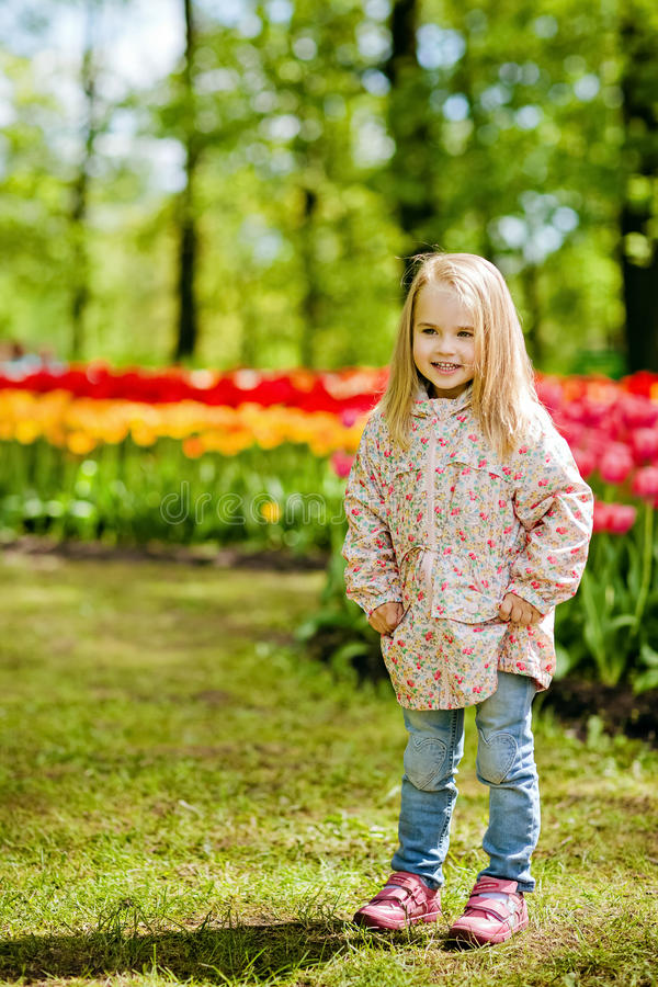 very cute beautiful girl blonde in pink coat stands near a flower bed of red tulips in a Park and smiling stock photos