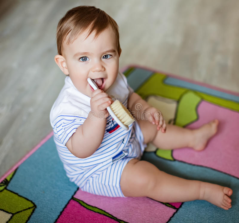 Very cute little blond boy chews on the brush for the hair, scratching his teeth, sitting on the colored carpet stock photography