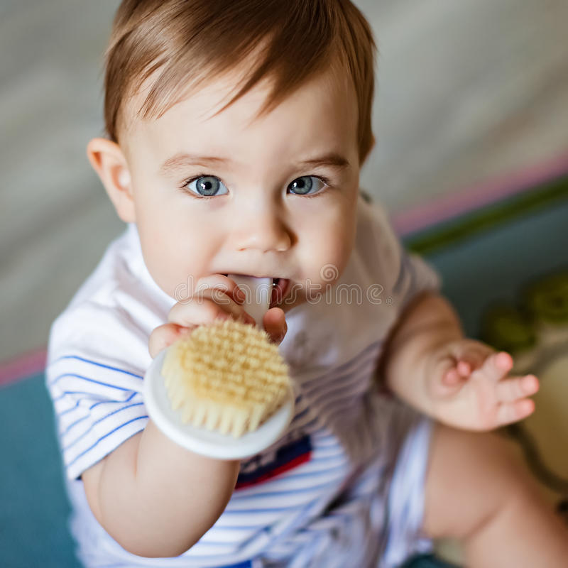 Very cute little blond boy chews on the brush for the hair, scratching his teeth, sitting on the colored carpet royalty free stock photos