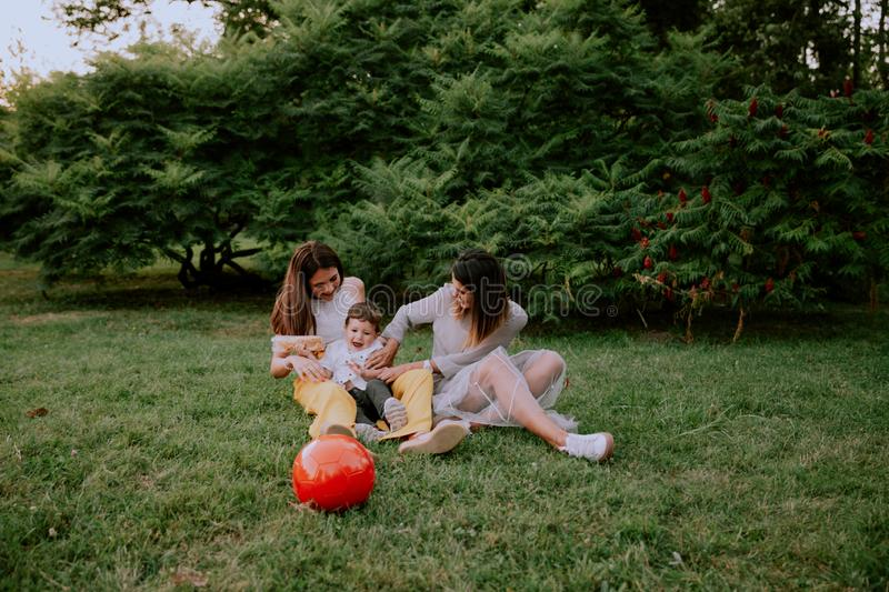 Very cute little boy and two smiling large attractive ladies enjoying the time in the park laying down on the grass royalty free stock photography