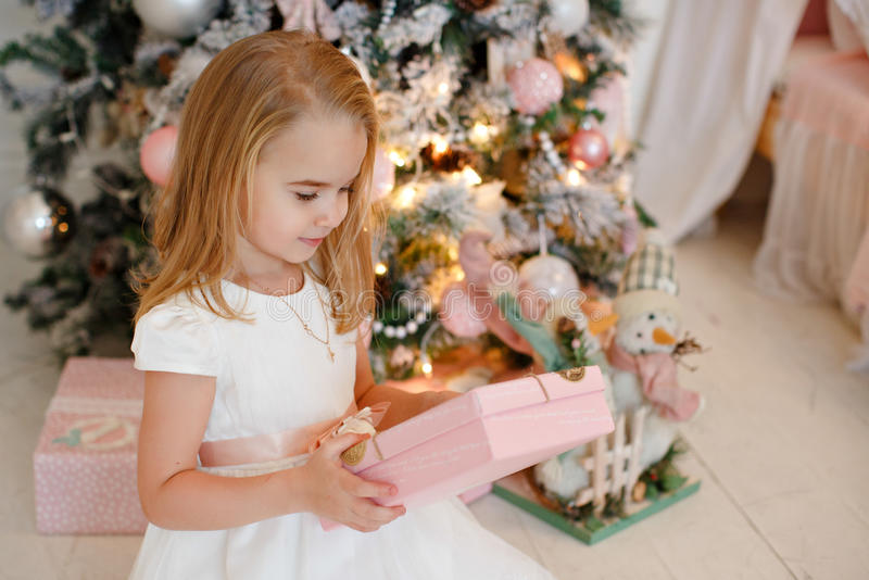 Very cute little girl blonde in a white dress holding a gift box stock photos