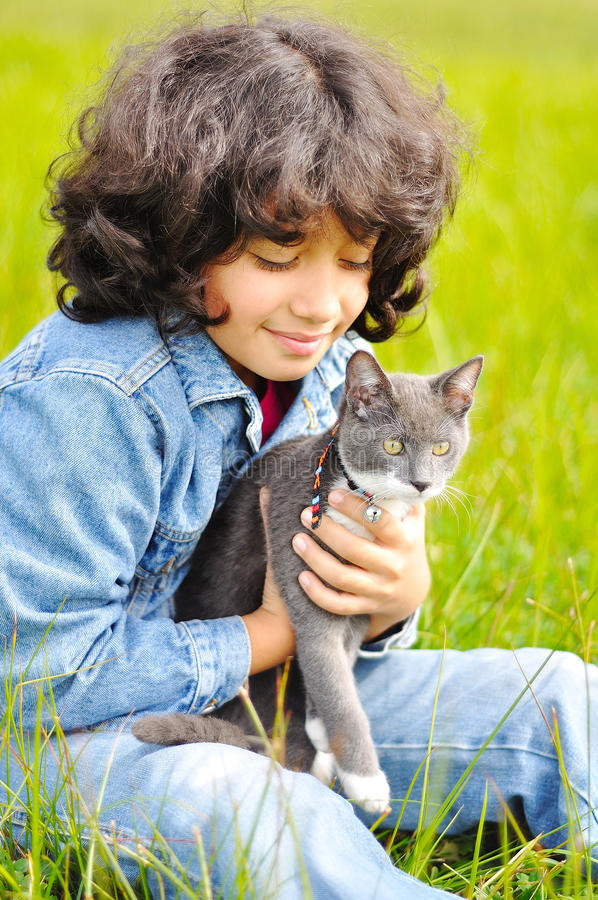 Very cute little girl with cat on meadow stock photo