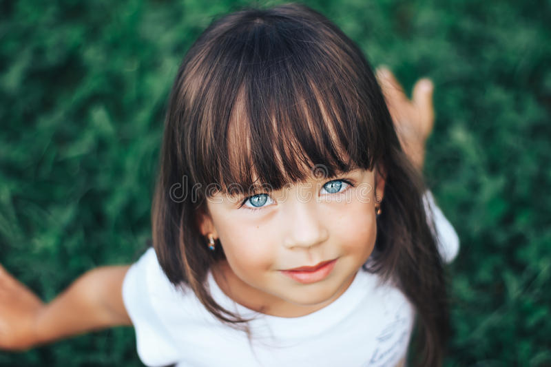 Download Close Portrait Of Very Beautiful Little Girl With A Bang Dark Hair And Blue
