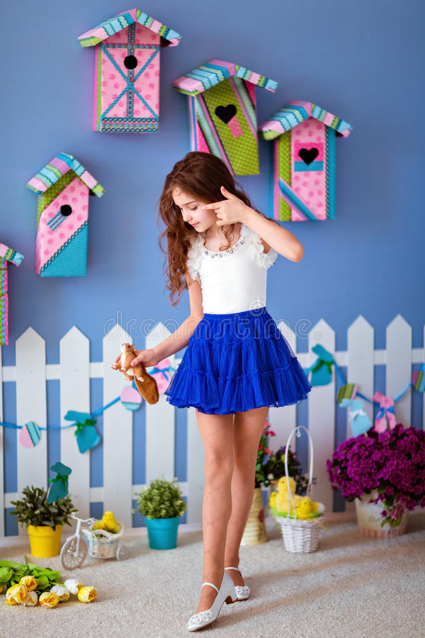 Very cute long-haired young girl in a blue skirt with Chicks for stock photography