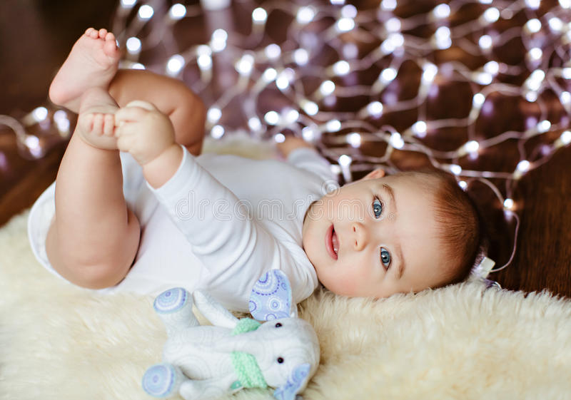 Very cute plump baby lying on the floor on the background of Christmas lights and she holds her legs royalty free stock images