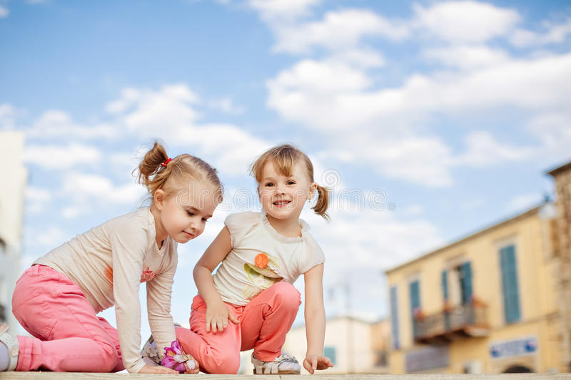 Very cute two girls with ponytails on her head and pink jeans si royalty free stock photo