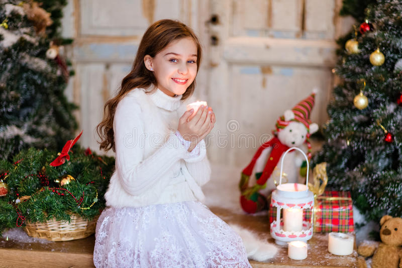 Very cute young long-haired girl in the white sweater holding a royalty free stock images