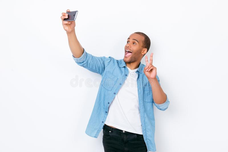 Very excited young african hipster in casual jeans wear is making selfie shot on camera of his pda, standing on a pure white back. Ground, showing peace sign stock photos