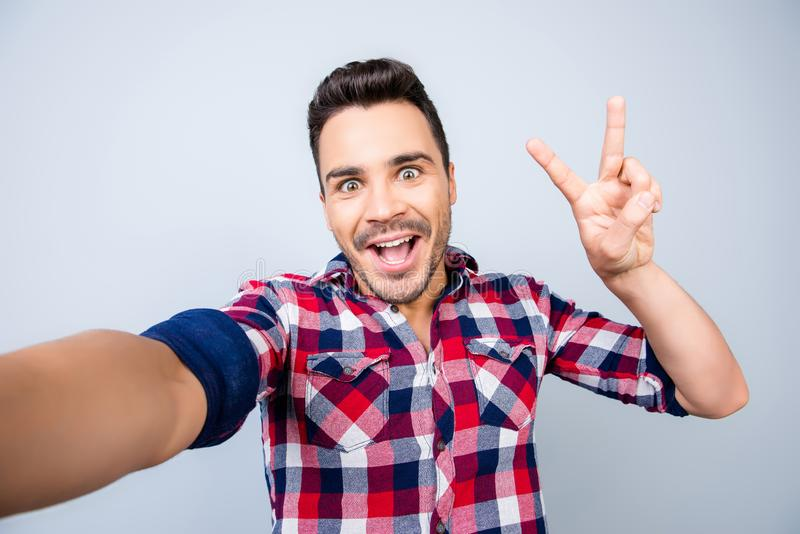 Very excited young hipster in casual wear is making selfie shot. On camera, standing on a pure background, showing peace sign, amazed, funky crazy mood royalty free stock photography