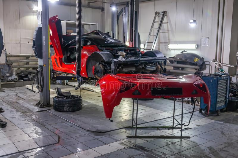 Very expensive and powerful sports car of red color, disassembled for repair, lifted on a lift in auto service, next to it is a royalty free stock photography