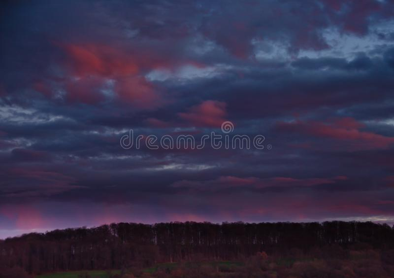 A very extraordinary and beautiful sunset in orange and purple colours. Lightened and bright stock photography