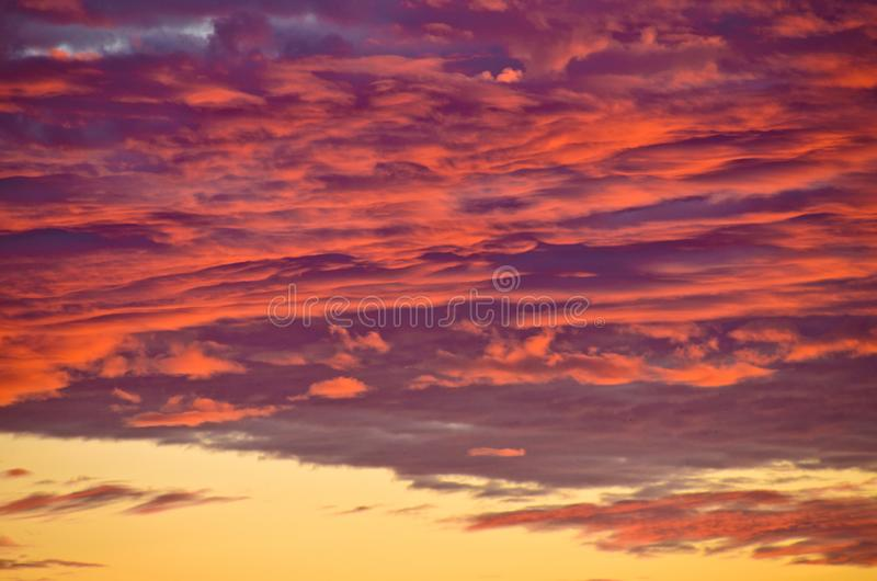 A very extraordinary and beautiful sunset in orange and purple colours. Lightened and bright royalty free stock image