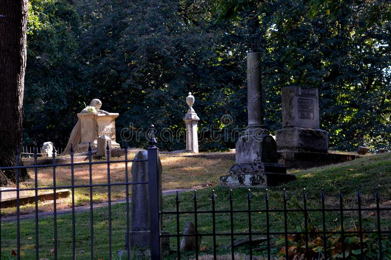 Weeping lady among her peers. A very famous grave marker with many ghost stories about it . Here we see her from outside the graveyard fence highlighted by a stock photos