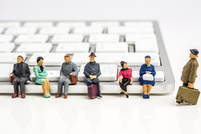Very fast technology changes. Closeup of miniature figurine of people sitting on white keyboard on white background stock images