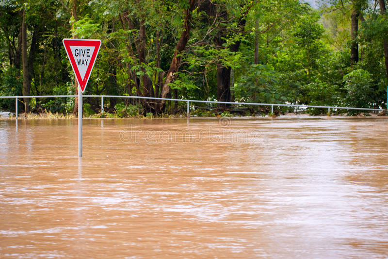 Very flooded road and give way sign