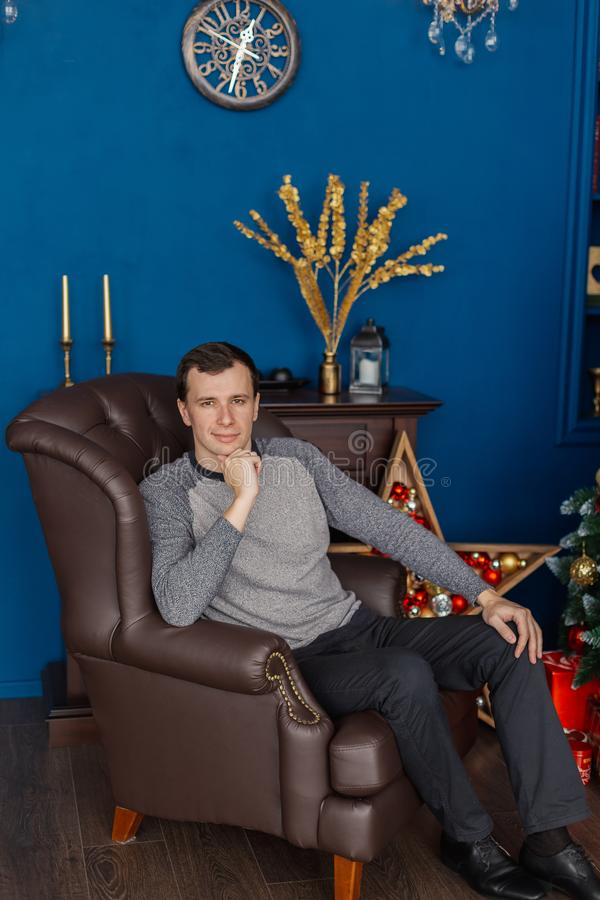 Very handsome man sitting on a leather chair in the New Year`s room. Very handsome man sitting on a leather chair in the New Year`s room royalty free stock images