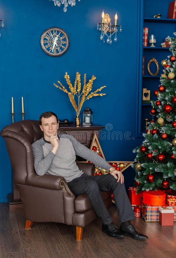Very handsome man sitting on a leather chair in the New Year`s room. Very handsome man sitting on a leather chair in the New Year`s room stock photography