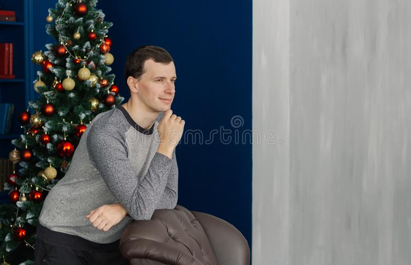 Very handsome man is standing by the chair in the New Year`s room. Very handsome man is standing by the chair in the New Year`s room royalty free stock photo