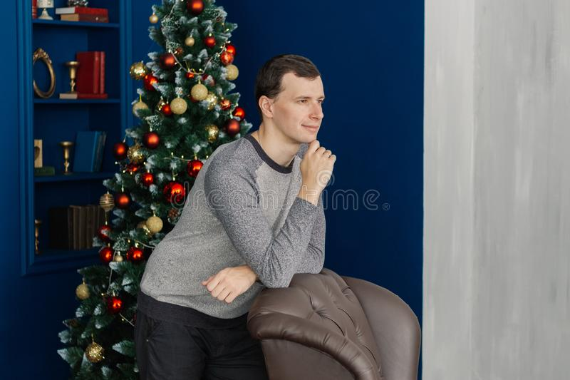 Very handsome man is standing by the chair in the New Year`s room. Very handsome man is standing by the chair in the New Year`s room royalty free stock photography