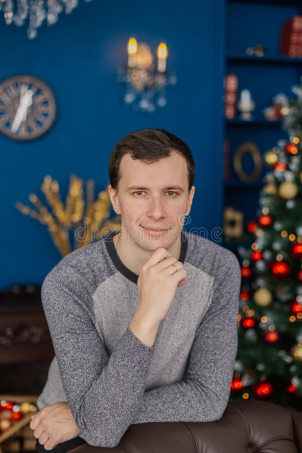 Very handsome man is standing by the chair in the New Year`s room. Very handsome man is standing by the chair in the New Year`s room stock photos