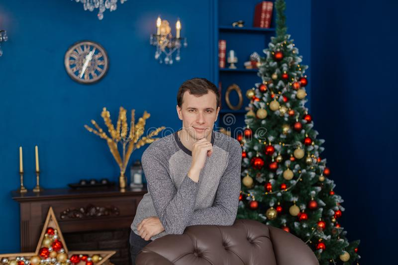 Very handsome man is standing by the chair in the New Year`s room. Very handsome man is standing by the chair in the New Year`s room royalty free stock images