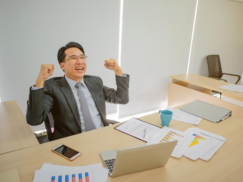 Very Happy asian business man sitting on his desk royalty free stock image