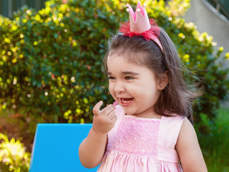 Very happy baby toddler girl, eating gummies laughing and smiling in outdoor party dressed in pink dress. As princess or queen with crown stock photography