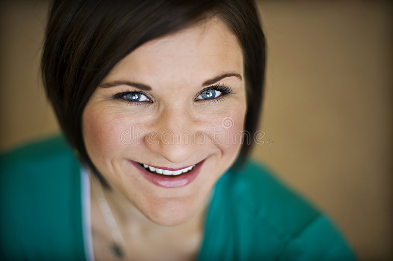 Very happy blue eyed brunette. Caucasian woman with short brown hair, light blue eyes and dimple smiling happily stock image